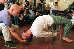 "During a press conference held by the Israeli human rights group B'Tselem, actors demonstrate the Israeli Shin Bet torture method known as ""Banana b'kiseh,"" where a detainee with hands and feet cuffed is painfully stretched, in the shape of a banana, over a chair by his jailer."